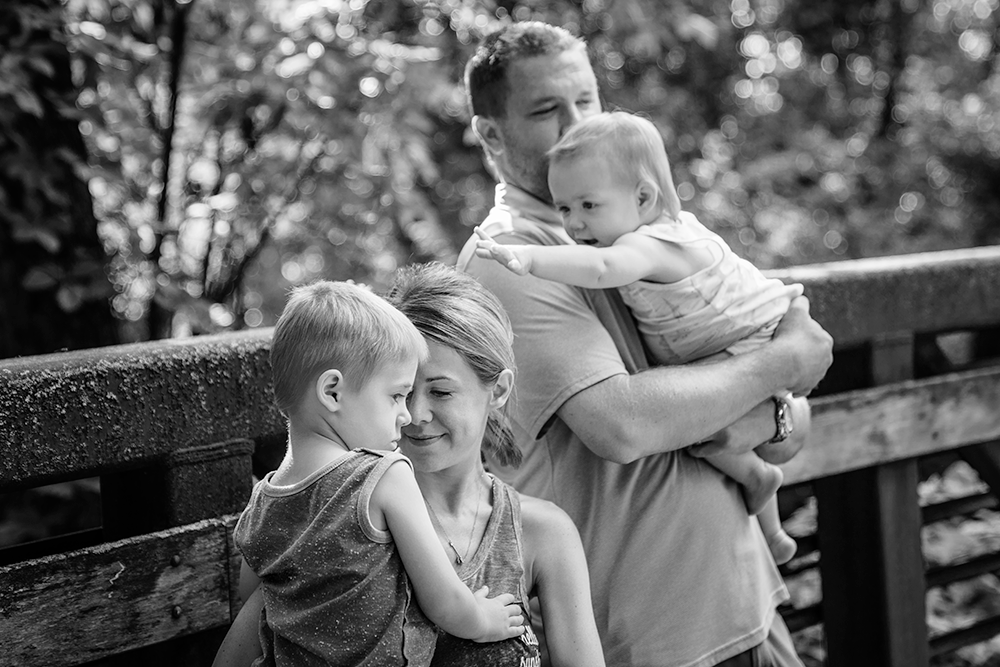 Lindsay and her family share a moment on the bridge at Mill Creek Streamway Park.